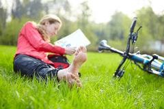 Girl cyclist on a halt reads lying in fresh green  Stock Photography