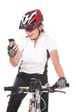 Girl Cyclist talking on the phone. Young woman biker with her bike isolated over white background looking at the phone Royalty Free Stock Image