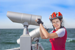 Girl in cyclist uniform and big spyglass Stock Image