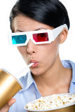 Girl in 3D glasses with beverage and popcorn Stock Images