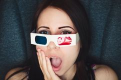 Girl with 3D glasses watches movie with shocked face in cinema. Close up Royalty Free Stock Photography