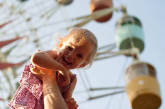 Girl on dad hands near the observation wheel Stock Photo