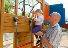 Girl with dad on  playground. Royalty Free Stock Photography
