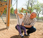 Girl with dad on  playground. Royalty Free Stock Image