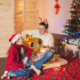 Girl with a dad playing the guitar and singing near christmas tr Stock Photo