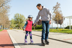 Girl and dad on roller skates Stock Photos