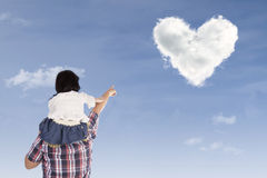 Girl on dad's back pointing at heart stock image