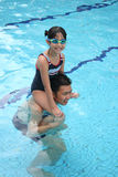 Girl on dad's shoulder. In the pool Stock Photo