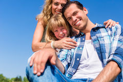 Girl on dads lap, Mom sitting next to them in field Royalty Free Stock Photography