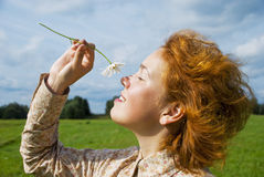 Girl with daisy. Smiling girl with daisy in a field Royalty Free Stock Photos