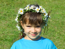 Girl with daisy chain on head. Happy young girl with daisy chain around head, green lawn in background Stock Photo