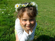 Girl with daisy chain on head. Portrait of cute young girl with daisy chain on head and green grass in background Stock Photos