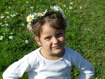 Girl with daisy chain on head. Cute young girl with daisy chain on head, green grass or field in background Stock Image