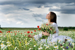 Girl in daisy field. Young happy girl with bouquet in daisy field royalty free stock photo