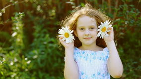 Girl with daisy in her hair in summer park. stock video footage