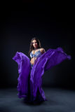 Girl dance in dark - oriental flying purple cloth Royalty Free Stock Images