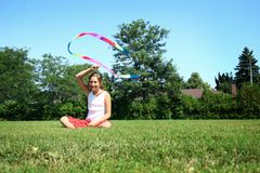 Girl with dance streamer. Young girl playing with long rainbow colored dance streamer on lawn Royalty Free Stock Photos