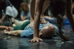 Dancer perform bodywork. A girl dancer performs a somatic bodywork or a massage for another dancer lying on the floor stock photos
