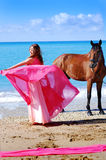 The girl dances on beach in red dress. Nearby there is horse Royalty Free Stock Photography