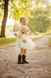 Little girl holding bear Stock Images