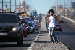 Girl dances on highway middle Stock Images