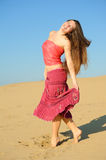 Girl dances on the sand. Girl in bright dress dances on the sand Stock Image