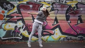 The girl dances in the street against the background of graffiti. stock video footage