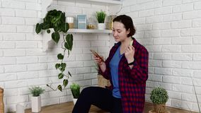 Girl dances to phone music and eats celery in kitchen. Pretty brunette girl in plaid shirt dances to smartphone music and eats celery in kitchen with pot flowers stock video footage