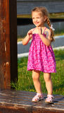 Girl dancing. Little happy (smiling) girl dancing outdoor on a wooden bench in a park royalty free stock photos