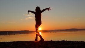 Girl dancing on the beach in the evening at sunset stock footage