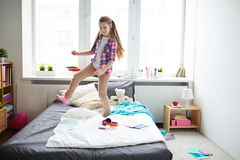Girl dancing on bed Stock Image