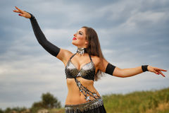 Girl dancing belly dance. Oriental Beauty belly dancer. Nice girl in national dress dancing in the open air. Nomads Royalty Free Stock Photography