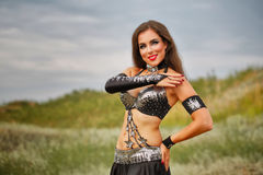 Girl dancing belly dance. Oriental Beauty belly dancing. Nice girl in national dress dancing in the open air. Nomads Stock Photos