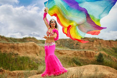 Girl dancing belly dance with a shawl. Oriental Beauty belly dancer. Nice girl in national dress dancing with shawl outdoors. Nomads Stock Photo