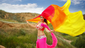 Girl dancing belly dance with a shawl. Oriental Beauty belly dancing. Nice girl in national dress dancing with shawl outdoors. Nomads Stock Images