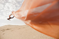 Girl dancing with big orange cloth Royalty Free Stock Image