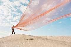 Girl dancing with big orange cloth Royalty Free Stock Images