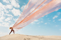 Girl dancing with big orange cloth Stock Photography