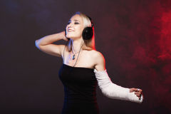 Girl dancing with broken arm and headphones Royalty Free Stock Images
