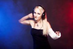 Girl dancing with broken arm and headphones Stock Images
