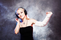 Girl dancing with broken arm and headphones Royalty Free Stock Photos