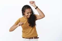 Girl dancing carefree not giving care if anyone watching having fun showing cool dance moves as shaking body and raising. Hands smiling delighted looking down stock photos