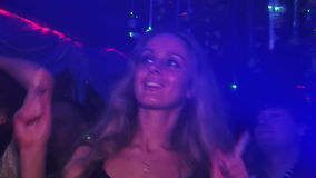 Girl dancing in a club at the party in the light