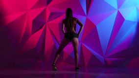 Girl dancing energetic dance booty in shorts on bright graphic background. Slow motion stock footage
