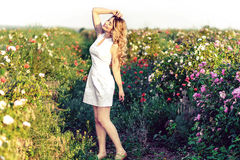 Girl dancing in a field of roses Stock Images