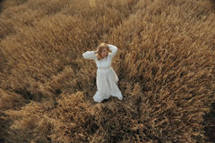 Girl dancing in  field in white dress Royalty Free Stock Image