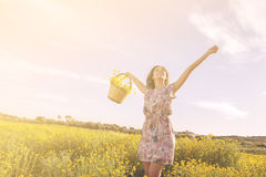 Girl dancing among flowers in a sunny day. Under a blue sky Royalty Free Stock Image