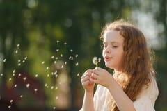 Girl dancing in flying dandelions outdoors. Stock Images