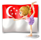 A girl dancing in front of the flag of Singapore Royalty Free Stock Photography