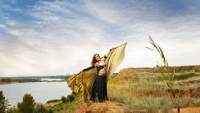 Girl dancing with golden wings. Oriental Beauty dance with wings. Nice girl in national dress dancing in the open air. Nomads Royalty Free Stock Photo